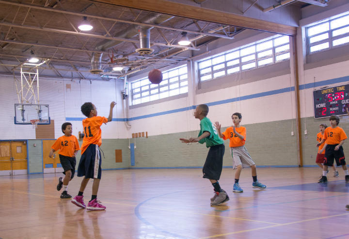four kids playing basketball in gym