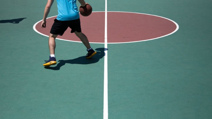 basketball player in yellow shoes dribbling at outdoor court