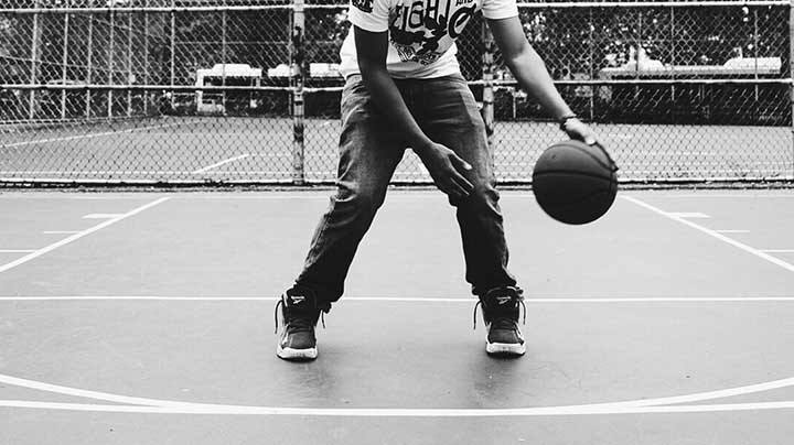 player dribbling basketball on outdoor court