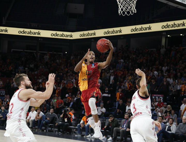 basketball player in red and yellow jersey finishing at basket with layup