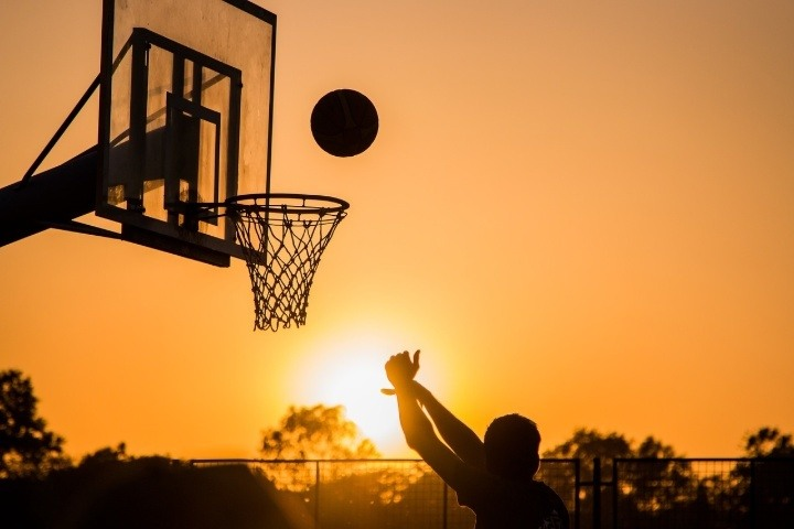 player shooting basketball at hoop outdoors at sunset