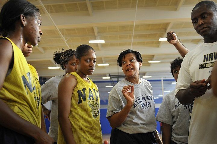 female basketball coach talking to girls team