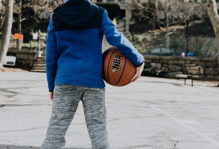 boy playing basketball on an outdoor court
