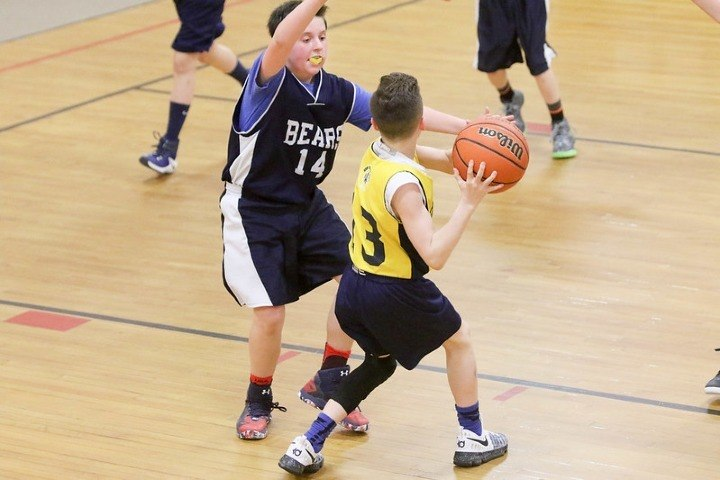 basketball player in yellow jersey pivoting in game
